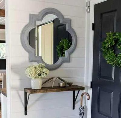 木制玄关柜配一只带有古典雕花的圆凳,加上墙上的木板画,显出浓厚的中